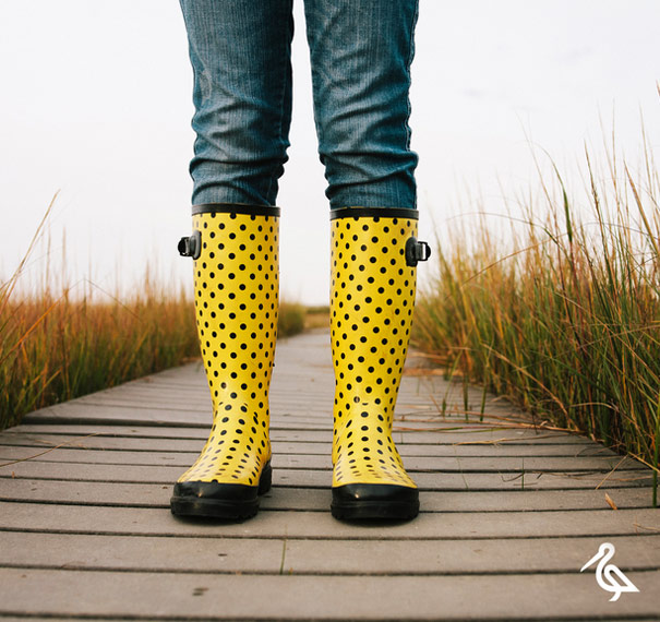 Person wearing bright yellow polka dot boots on a boardwalk